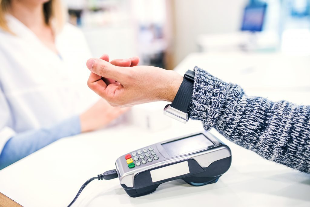 A customer making wireless or contactless payment using smartwatch.