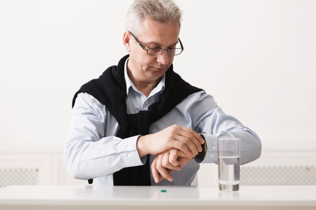 An elderly checks his smartwatch to see medication status