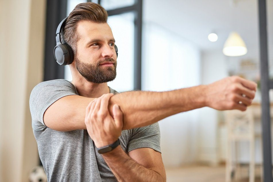 Man wear wireless headphones land smartwatch while doing exercise at home