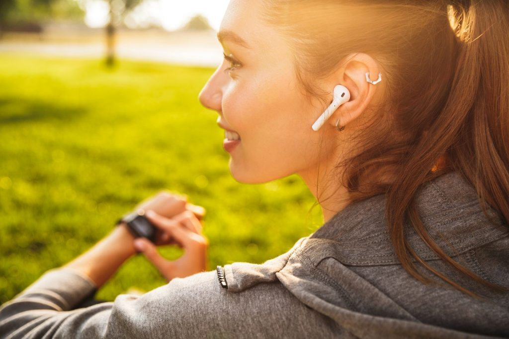 a woman use smartwatch and bluetooth earbud