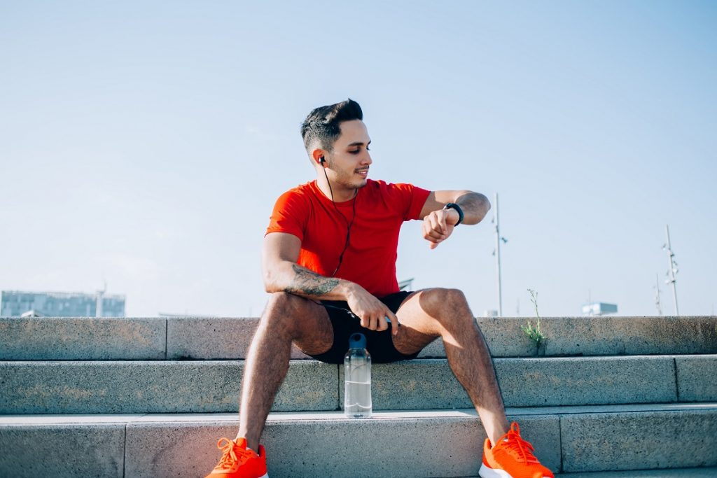 male trainer with water bottle checking smartwatch fitness results during workout break at urbanity, young runner in electronic headphones listening audio training during leisure for workout